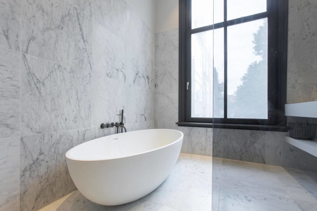 COCOON bathroom with white modern bathtub and marble stone